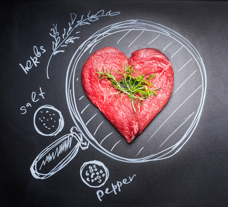 Heart shaped chop of meat on black chalkboard with  painted pan and ingredients, top view.For Meat lovers and eater