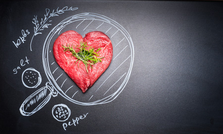 Hartvormige chop van vlees op zwart bord met geschilderde pan en ingrediënten, bovenaanzicht, plaats voor tekst. Voor vleesliefhebbers en eter