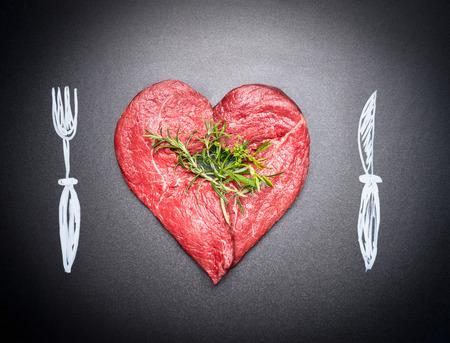심장 모양의 원시 절단 고기입니다. 칠한 칼 붙이로 고기 사랑 : 포크와 나이프. 어두운 칠판 배경입니다. 고기 애호가 및 먹는 사람들을위한