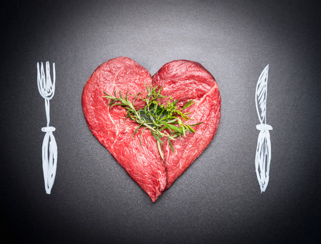 Heart shaped raw chop of meat. Meat love with  painted cutlery:  fork and knife. Dark chalkboard background . For Meat lovers and eater Banco de Imagens - 56462574