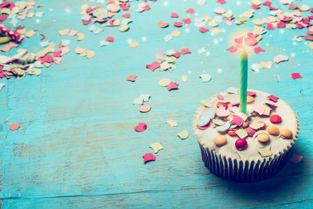 キャンドルとターコイズ ブルーみすぼらしいシックな木製背景に紙吹雪の誕生日ケーキ。誕生日お祝いグリーティング カード