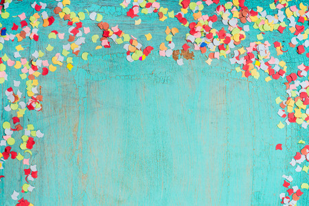 Colorful confetti on  turquoise blue background, border. Party background
