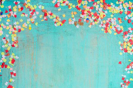 turquesa: confeti de colores sobre fondo azul turquesa, frontera. Parte de fondo Foto de archivo