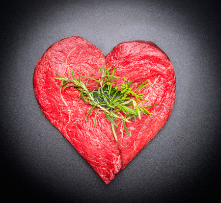 love shape: Heart shaped raw meat with fresh herbs on black chalkboard background, top view, close up. Healthy diet or organic meat food
