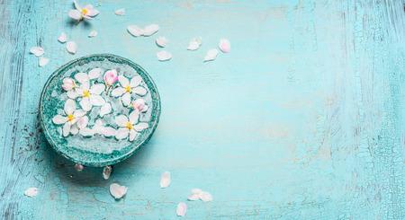 터키석 블루 초라한 세련된 나무 배경에 물 그릇에 흰색 꽃, 상위 뷰와 아름다운 봄 꽃. 웰빙과 스파 개념. 봄 꽃 배경, 배너