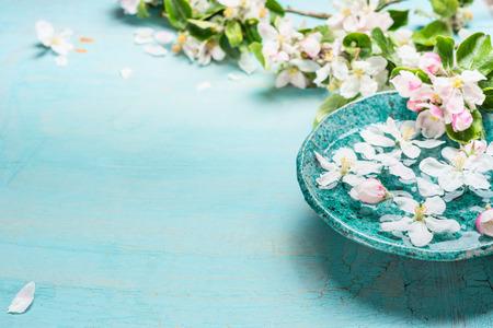 터키석 블루 초라한 세련된 나무 배경에 물과 하얀 벚꽃 꽃과 아로마 그릇. 웰빙과 스파 개념. 봄 꽃 배경 스톡 콘텐츠