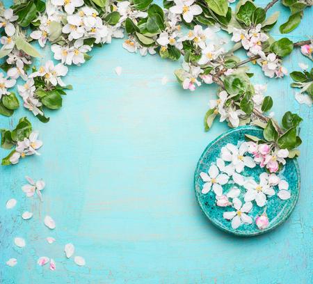 Spa oder Wellness türkis Hintergrund mit Blüten und Wasser Schüssel mit weißen Blüten, Draufsicht. Frühlingsblütenhintergrund Standard-Bild