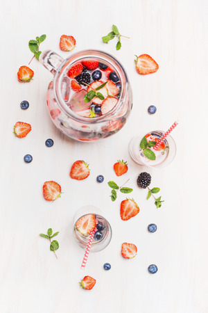 boire l'été avec des baies et des cubes de glace. Pichet ou un pichet de limonade baies, verres, de la paille et des ingrédients sur le fond en bois blanc, vue de dessus. Saine boisson vitaminée.