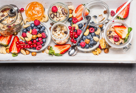 Havermout met bessen en noten in glazen potten, bovenaanzicht. Gezond ontbijt, concept sportvoeding of dieet voedsel