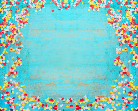 greening: Turquoise blue party background with confetti. Frame of confetti on shabby chic wooden background. Festive greening card. Invitation background