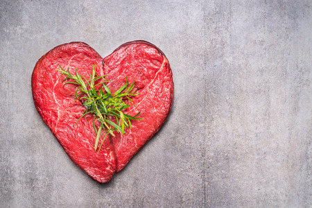 food concept: Heart shape raw meat with herbs and text on gray concrete background , top view, horizontal