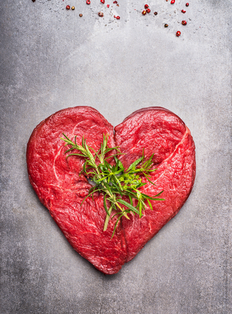 Heart shape raw meat with herbs and text on gray concrete background, top view, vertical