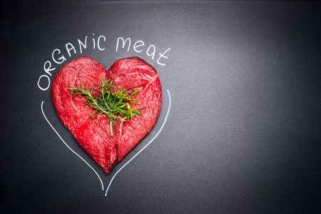 meat lover: Organic meat for healthy Eating. Heart shape raw meat with herbs and text on black blank chalkboard background, top view Stock Photo