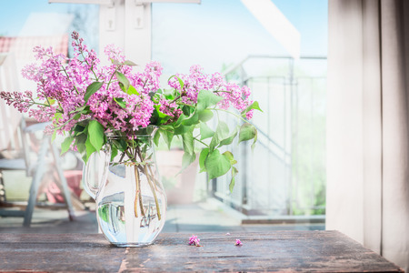 front desk: Home interior with Bouquet  of blooming lilac flowers on the table in front of window Stock Photo