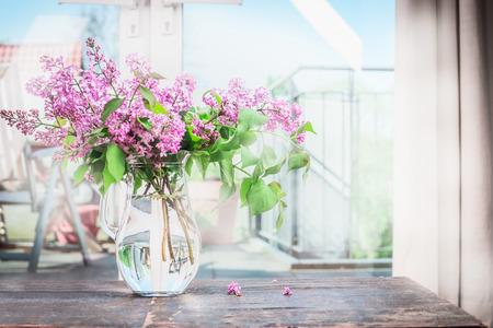 Wnętrze domu z bukietem kwitnące kwiaty bzu na stole naprzeciwko okna