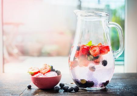 Kruik met zomer drankje met water en bessen. Bessen limonade op het terras tafel over de natuur achtergrond. Detox drank, voeding en gezondheid food concept