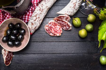Rodajas de salchichón italiano con aceitunas verdes y negras antipasti y vino rojo sobre fondo negro de madera, vista desde arriba, el lugar de texto. Fondo de la comida italiana Foto de archivo