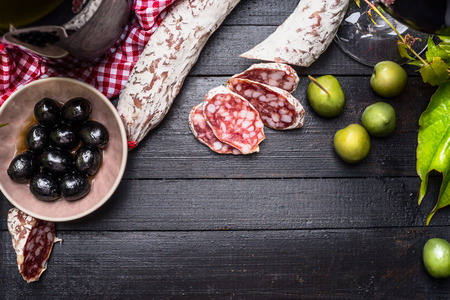 antipasto platter: Sliced italian salami with green and black olives antipasti and red wine on black wooden background, top view, place for text.  Italian food background