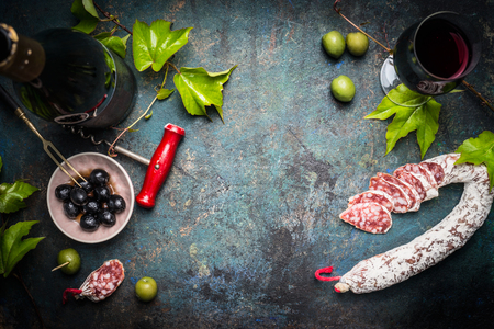 italian: Italian still life with salami, red wine, olives and grape leaves on dark rustic background, top view, place for text. Italian food background