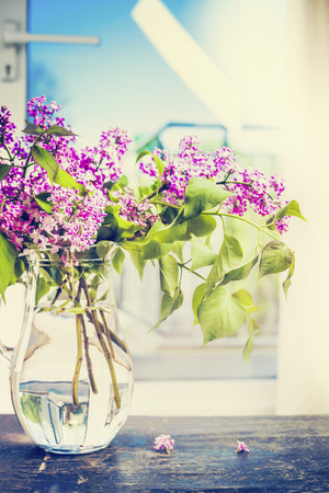 old windows: Bouquet of lilac in a glass jug on the table over window background. Home decoration