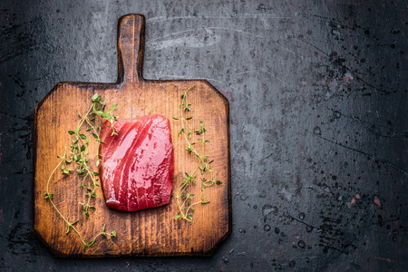 herbst: Tuna steak for grill or  frying on wooden cutting board and dark rustic  background with fresh herbst, top view, close up. Seafood concept