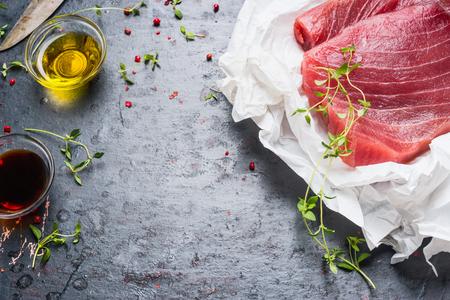 De tonijnbiefstukken in verpakkend document met het koken van ingrediënten op donkere rustieke achtergrond, sluiten omhoog. Zeevruchten concept Stockfoto