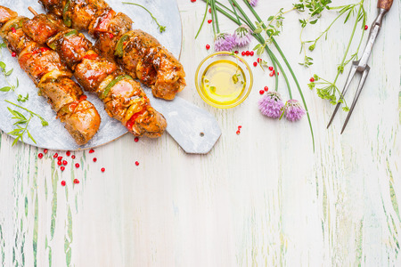 bbq background: Grill or BBQ preparation with Meat skewers  and ingredients on light rustic background, top view, border