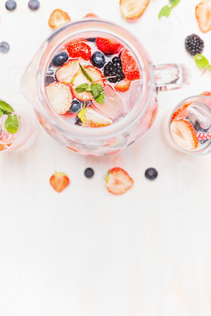 red white and blue: Jug with fresh berries lemonade on white wooden background, top view, border