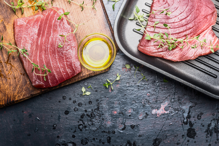 Tuna steak preparation on dark aged vintage background, top view Seafood concept
