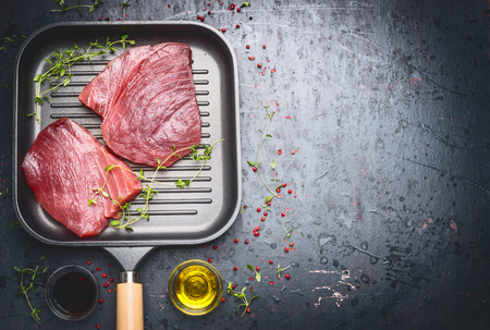 Raw Tuna Steak in grill frying pan with herbs and oil on dark aged vintage background, top view, place for text Stock Photo