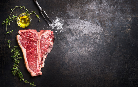 Raw T-bone Steak with fresh herbs and oil on dark rust metal background, top view, place for text, horizontal Foto de archivo
