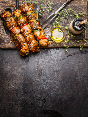Marinated meat skewers with vegetables for grill or BBQ , fresh seasoning nad oil on dark rustic wooden background, top view, place for text, border, vertical