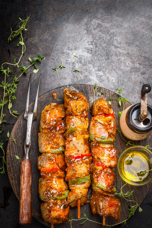 Grill time with marinated skewers, meat fork, herbs spices and oil on dark rust metal background, top view, place for text