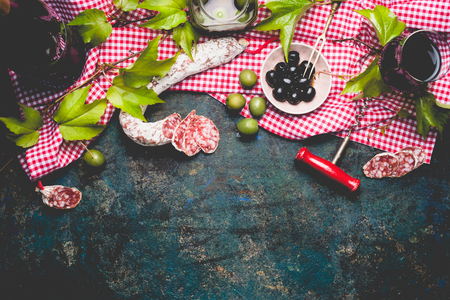 glass of red wine: Italian appetizer snack on red cell cotton tablecloths with salami, olives and red wine, dark rustic background, top view, border