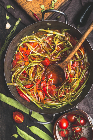 Sliced  green French beans dish with tomatoes sauce and wooden cooking spoon. Stewed French beans spaghetti  in vintage cooking pot on dark rustic background, top view.  Vegetarian food concept