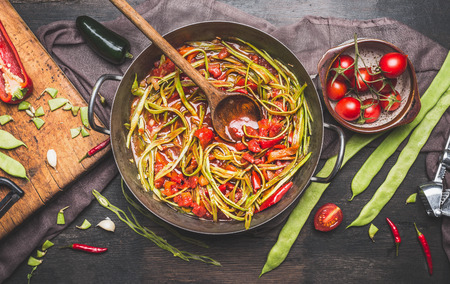 Green French beans meal preparation with wooden spoon. Green French beans in cooking pot with tomatoes sauce and ingredients on dark rustic background, top view.  Vegetarian food concept