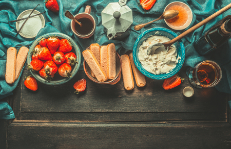rustic kitchen: Unadulterated italian strawberry tiramisu cooking ingredients on dark rustic kitchen table, top view, place for text. Italian food concept, border