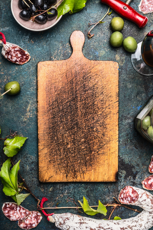 coking: Italian food and antipasti around old wooden cutting board, top view. Italian food background for menu or coking recipes, frame
