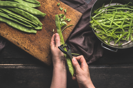 Green french beans,  preparation on dark kitchen table. Woman Female hands cut beans with vegetable peeler. Cutting board with Green french beans and sliced beans , top view