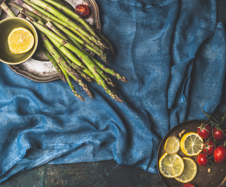 italian cuisine: Asparagus and cooking ingredients on dark blue background, top view, place for text