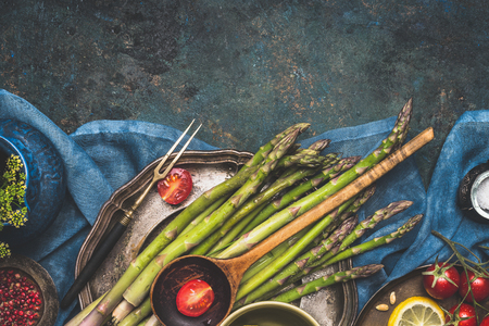 Food border with green asparagus, tomatoes,lemon and other ingredients for tasty asparagus cooking. Green asparagus preparation on dark rustic background, top view, place for text, border
