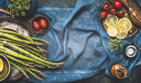 Green asparagus and vegetables cooking ingredients on dark blue rustic background, top view, place for text, banner