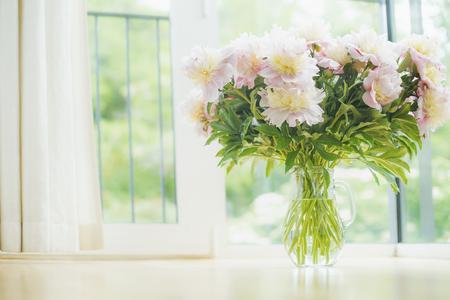 Duże piękne jasnoróżowe piwonie bukiet w szklanych wazonie na tle okna. Światło wnętrz z kwiatów i wazon. Living room interior