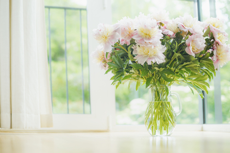 Big beautiful pale pink peonies bouquet in glass vase over window background. Light Home  decoration with flowers and vase. Living room interior