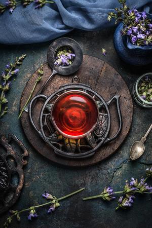 Tasse Gesunde Kräuter-Detox-Tee mit Salbei Blätter und Blumen auf dunklem Hintergrund rustikalen, Draufsicht. Gesunde Getränke, Entgiftung oder reinigen Food-Konzept