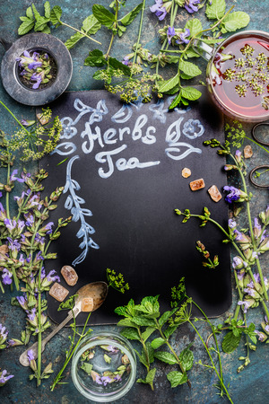 Lettering Herbal Tea on dark chalkboard. Various fresh herbs, tea tools and cup of tea on dark vintage background, frame, top view. Healthy drinks, detox or clean food concept