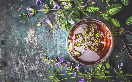 Cup of herbal tea on dark aged rustic background, top view, place for text, border Standard-Bild