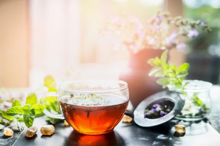 Taza de té de hierbas caliente en la ventana todavía en fondo de naturaleza soleado, horizontal. escena casa con bebida caliente. Detox o limpia el concepto de alimentos