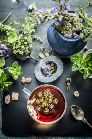 herbal background: Cup of herbal tea with tea tools and various fresh herbs on dark aged background, top view. Healthy drinks, detox or clean food concept Stock Photo