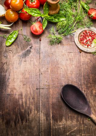 pimenton: Fondo de la comida mediterránea. Varios condimentos frescos y tomates con una cuchara de cocina de edad en el fondo de madera envejecida, vista desde arriba